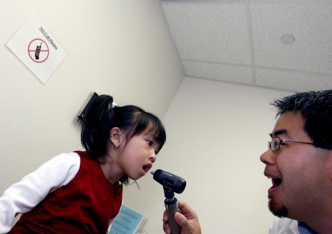Doctor examining a young girl